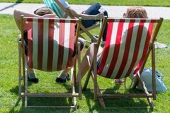 People relaxing in the sun in the UK during early May bank holiday. Couple sat on red and white deck chairs in UK park during summer sun royalty free stock image