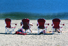 People relaxing and sunbathing in a row of beach chairs on the s. And in front of the ocean on a sunny summer day Stock Image