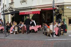People are relaxing at a sunny cafe terrace in the Old town of Vilnius, Lithuania Royalty Free Stock Image