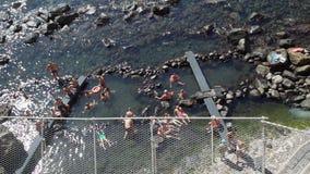 People Relaxing in Thermal Springs of Sorgeto Bay