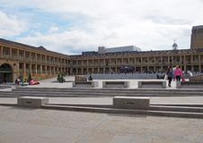 People relaxing in the town square around the piece hall in halifax west yorkshire. Halifax, west yorkshire, united kingdom - 31 may 2019: people relaxing in the stock photo