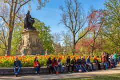 People relaxing in the Vondelpark. People relaxing at the Statue of Joost van den Vondel in the Vondelpark in Amsterdam the Netherlands royalty free stock photography