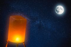 People Release Paper Fire Lamp rising over night sky full moon. At Loy Krathong Festival Thailand stock photography