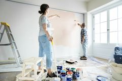 People renovating the house by painting the wall Stock Photo