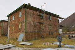 People repair building in the abandoned Russian arctic settlement Pyramiden, Norway. Stock Images