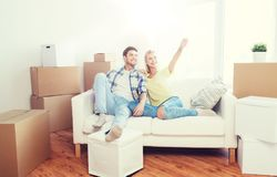 Couple with boxes moving to new home and dreaming. People, repair and real estate concept - smiling couple with boxes moving to new home and dreaming Stock Images