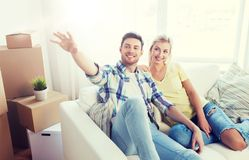 Couple with boxes moving to new home and dreaming. People, repair and real estate concept - smiling couple with boxes moving to new home and dreaming Royalty Free Stock Photos