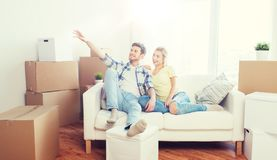 Couple with boxes moving to new home and dreaming. People, repair and real estate concept - smiling couple with boxes moving to new home and dreaming Royalty Free Stock Photo