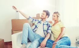 Couple with boxes moving to new home and dreaming Royalty Free Stock Image
