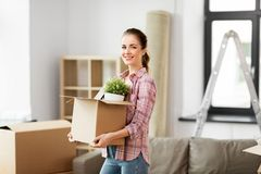 Happy woman with stuff moving to new home stock photos