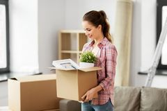 Happy woman with stuff moving to new home royalty free stock photo