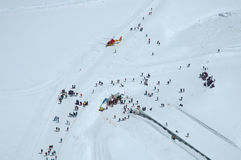 People and rescue helicopter on Jungfaujoch pass in Switzerland. Royalty Free Stock Image