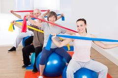 People with resistance bands sitting on fitness balls Royalty Free Stock Images