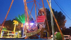 People rest in amusement park ride on a swing stilized as old sail boat