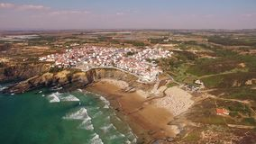 People rest on the beach naer Zambujeira de Mar, Portugal aerial view stock footage
