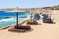 People rest on beach of Siva Sharm ex Savita Resort 5 * hotel in Sharks Bay, Sharm El Sheikh, Egypt. Warning red flag on beach. SHARM EL SHEIKH, EGYPT - MAY 8 Stock Photo