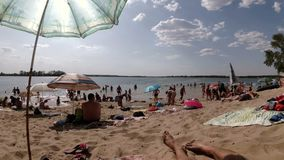 People Rest on the Beach. UKRAINE, KAMENSKOE, AUGUST 20, 2017: People rest on the beach. People lie on the sand under umbrellas near the river stock video