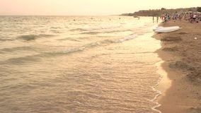 People rest on the evening beach. Sea waves and wet sand stock footage