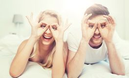 Happy couple lying in bed at home Stock Image