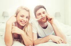 Happy couple lying in bed at home Stock Photos