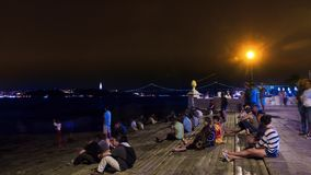 People rest at night on the waterfront of the River Tagus, Lisbon, timelapse stock video footage