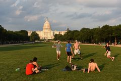 People rest and play the ball on the National Mall with United States Capitol on the background. stock images