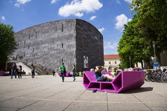 People rest on red benches in front of the MUMOK, Museum of modern art  at the MuseumsQuartier Stock Images