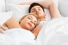 Happy couple sleeping in bed at home. People, rest and relationships concept - happy couple sleeping in bed at home stock photography