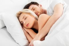 Happy couple sleeping in bed at home. People, rest and relationships concept - happy couple sleeping in bed at home stock photos