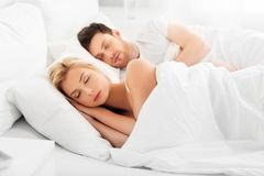 Happy couple sleeping in bed at home. People, rest and relationships concept - happy couple sleeping in bed at home royalty free stock photography