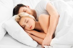 Happy couple sleeping in bed at home stock images