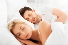 Happy couple sleeping in bed at home. People, rest and relationships concept - happy couple sleeping in bed at home royalty free stock photos