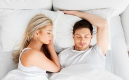 Happy couple sleeping in bed at home. People, rest and relationships concept - happy couple sleeping in bed at home royalty free stock photo