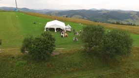 People rest at the white tent under the trees. Multicolored wildflowers grow on a glade in the mountains. The drone rises over the field stock footage