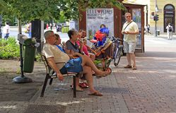 People are resting on a bench outdoors in Debrecen, Hungary stock images