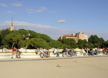 People resting on a bench in Park Guell Stock Images