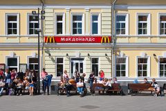 People resting on benches near McDonald's restaurant building Royalty Free Stock Photo