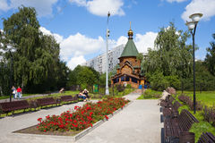 People resting on benches near a wooden cathedral Royalty Free Stock Images