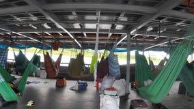 People resting in hammocks on passenger boat deck, Brazil stock footage
