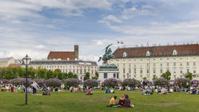 People resting on the lawn at the lawn. AUSTRIA,VIENNA - APRIL 17,2016:People resting on the lawn at the Hofburg in Vienna.Residence of the President of the royalty free stock photo
