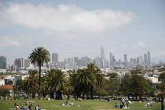 People resting in Mission Dolores Park with the view of skyscrapers of San Francisco stock image