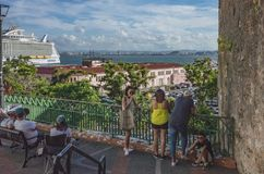 People resting in Old San Juan. San Juan, Puerto Rico, USA - Jan. 2, 2018: People resting by railing and enjoying a view of Old San Juan and the sea stock image
