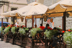 People resting in outdoor cafe in historic city centre. Lviv, Royalty Free Stock Photography