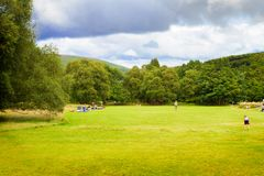 People resting and playing on fresh green park lawn, autumn, summer or spring season. Picnic in park, activity. Stock Photography