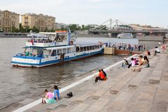 People resting on the riverbank. River ship is in the background Stock Photos