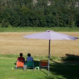 People resting in the shadow. People resting in chairs in the shadow of park umbrella, looking at withered crop field, view from the back Stock Images