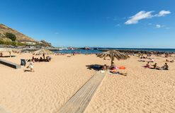 People are resting on a sunny day at the beach in Machico. Madeira Island Stock Image