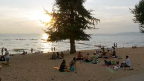 People are resting on the tropical beach at sunset. Pattaya, Thailand. PATTAYA, THAILAND, DECEMBER 14, 2017: People are resting on the tropical beach at sunset stock video