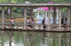 People are resting in water pavillion on the lake, Kunming, China. Kunming, China - June 8, 2015: people are resting in water pavillion on the lake, Kunming stock photography
