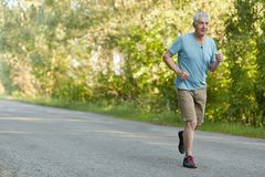 People, retirement and sport motivation concept. Healthy fit grey haired male pensioner runs on asphalt, listens favourite melody. In earphones, enjoys leisure Royalty Free Stock Photography